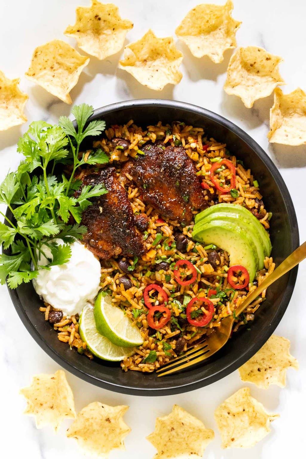 Vertical overhead photo of One-Pot Mexican Chicken and Rice in a brasier skillet surrounded by tortilla chips.
