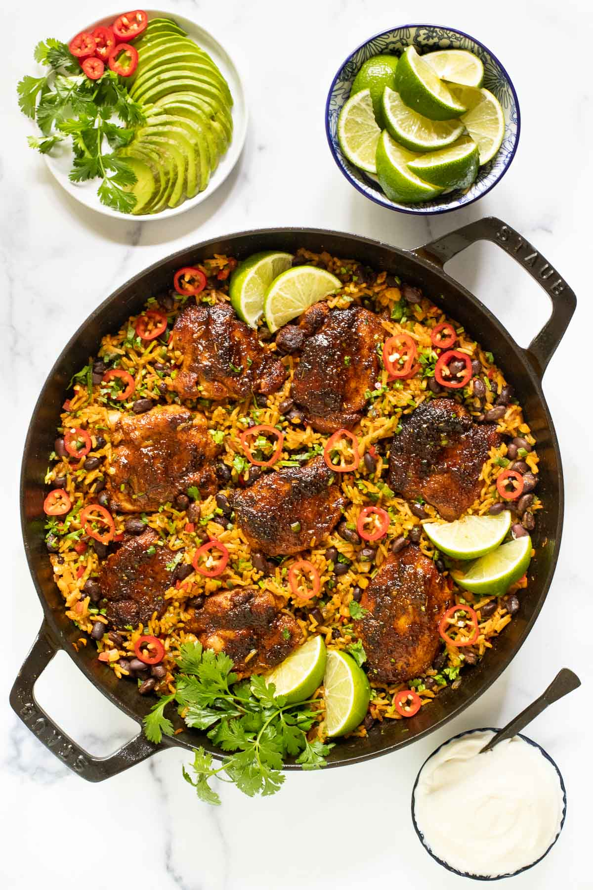 Vertical overhead photo of One-Pot Mexican Chicken and Rice surrounded by garnishes including sliced avocados, peppers, cilantro, lime wedges and sour cream.