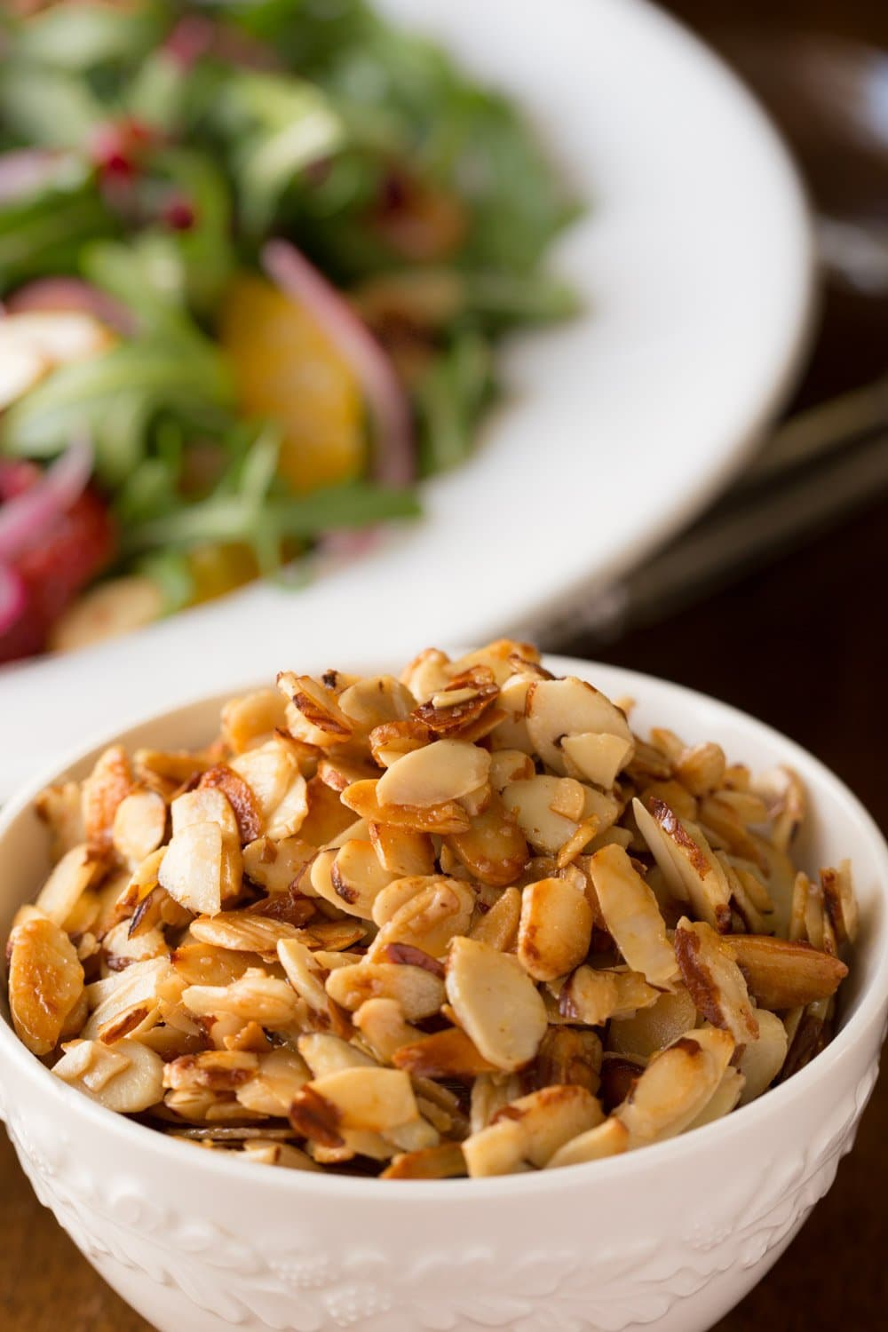 Vertical closeup photo of Honey Glazed Almonds in a small white serving bowl with a salad in the background.