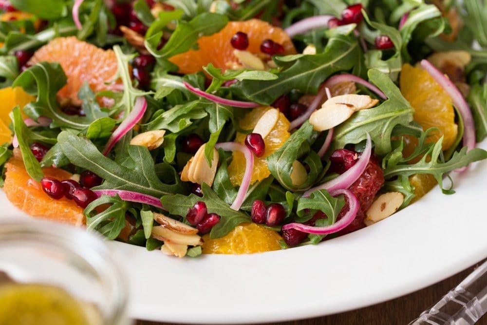 Horizontal closeup photo of an Arugula Orange Salad with Lemon Ginger Salad Dressing in a white serving bowl.