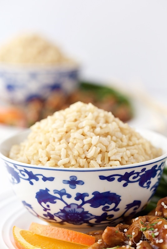 Easy Orange Chicken with Brown Rice - a super delicious dinner you can have on the table in no time flat. A few secret ingredients make the chicken incredibly tender! thecafesucrefarine.com