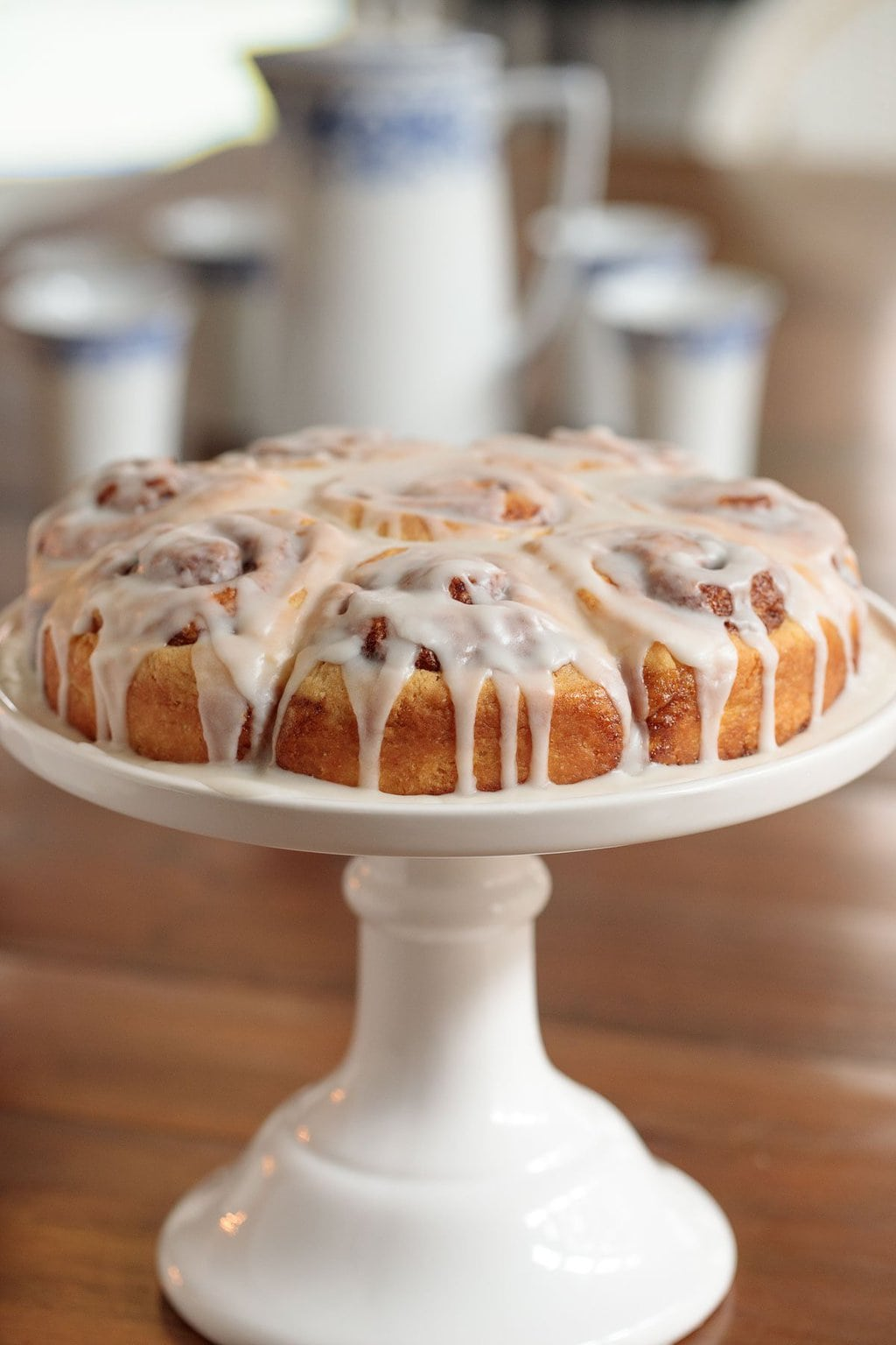 Vertical picture of overnight cinnamon rolls on a white cakestand