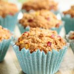 Vertical picture of peach crumble muffins in turquoise muffin liners