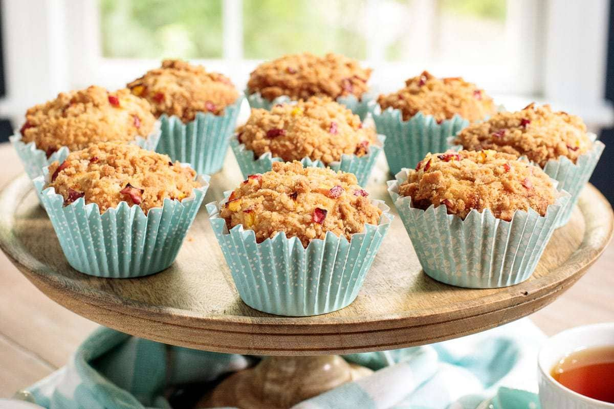 Horizontal closeup photo of Peach Crumble Muffins in turquoise muffin liners on a wood pedestal plate.