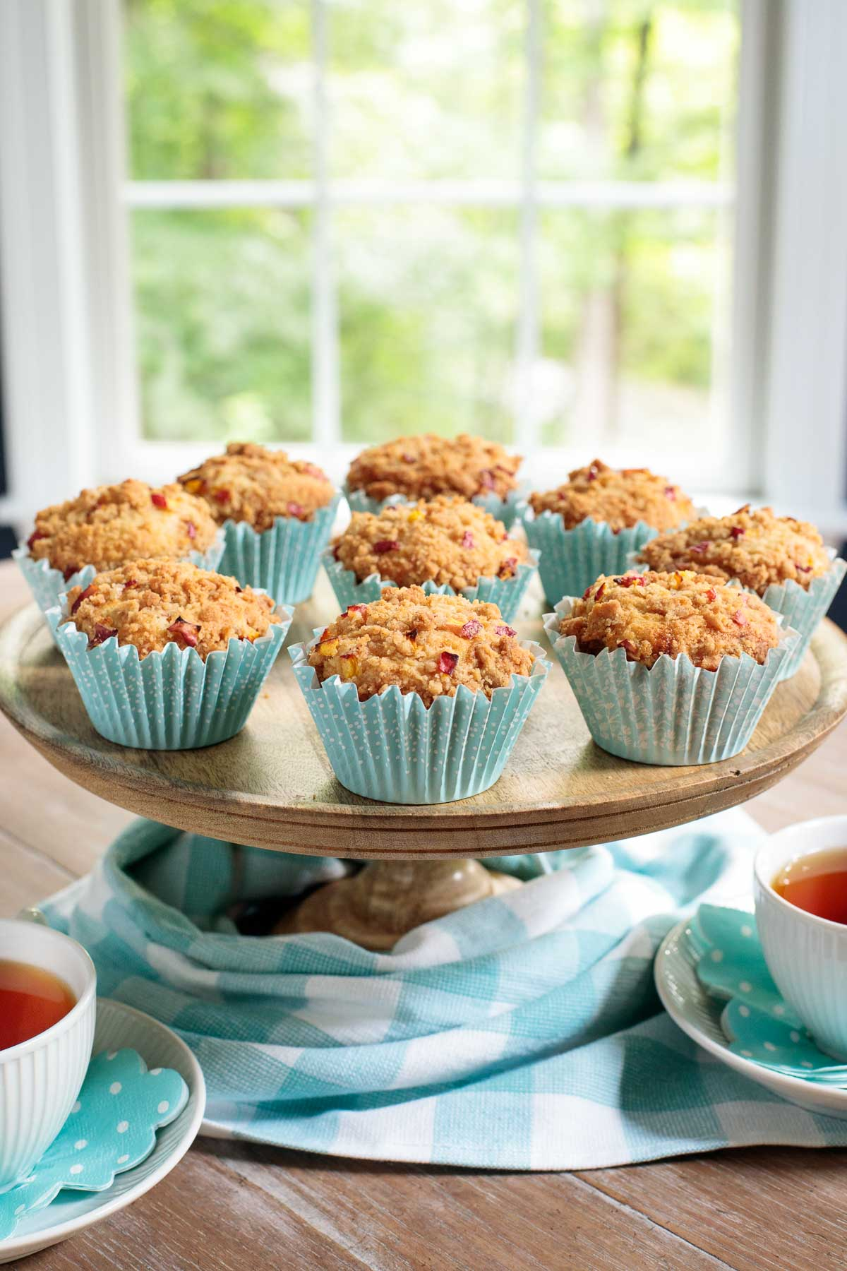 Vertical photo of a wooden cake stand filled with Easy Peach Crumble Muffins surrounded by cups of tea and a turquoise checkered cloth.