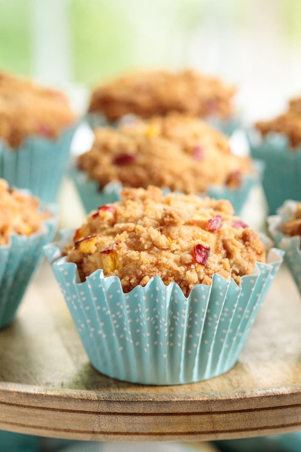 Extreme closeup photo of a serving pedestal filled with Easy Peach Crumble Muffins in turquoise patterned cupcake liners.