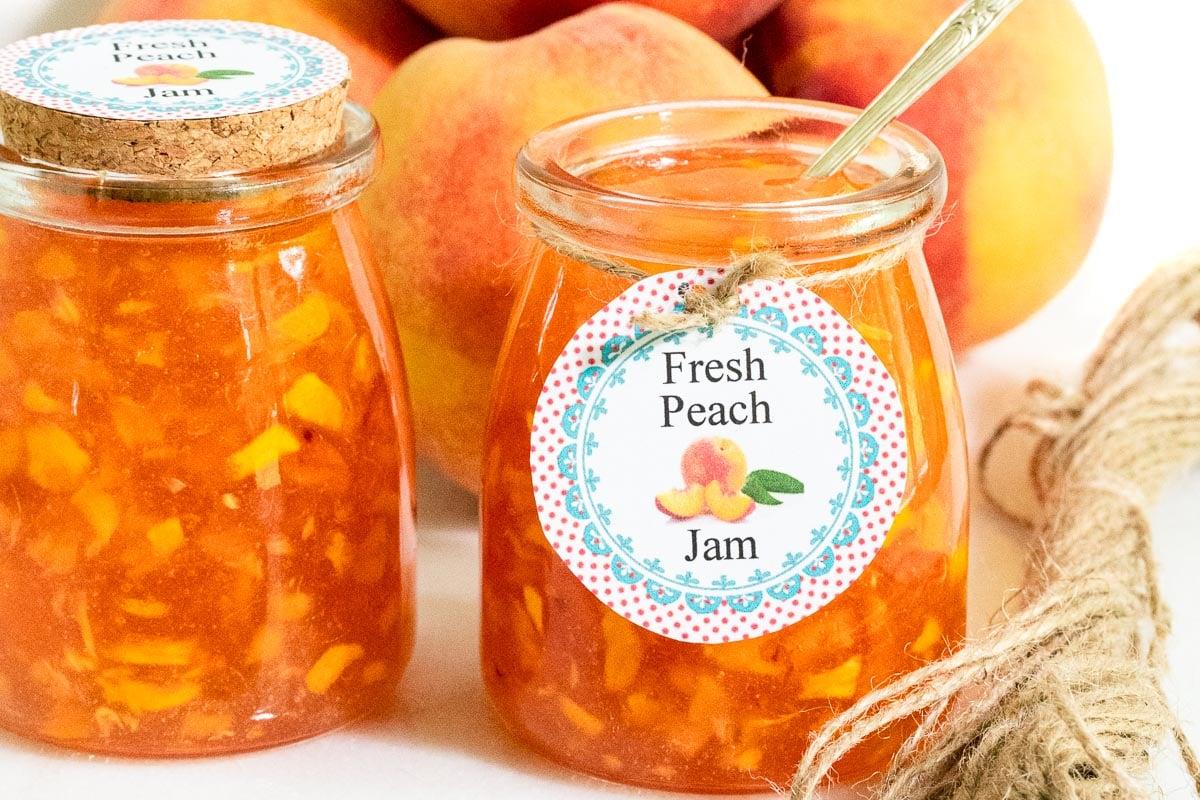 Horizontal closeup photo of jars of Easy Peach Freezer Jam with custom gift labels.