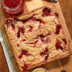 Overhead picture of peanut butter and jelly blondies on a wooden cutting board