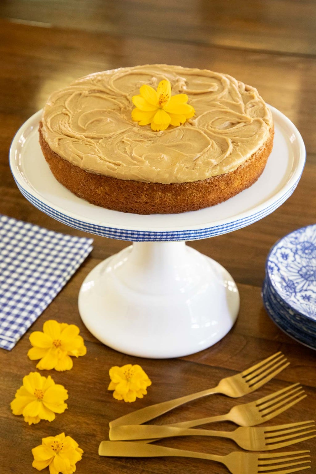 """Vertical photo of a Peanut Butter Texas Sheet Cake that was baked in a round 8"""" pan and placed on a white pedestal cake stand."""