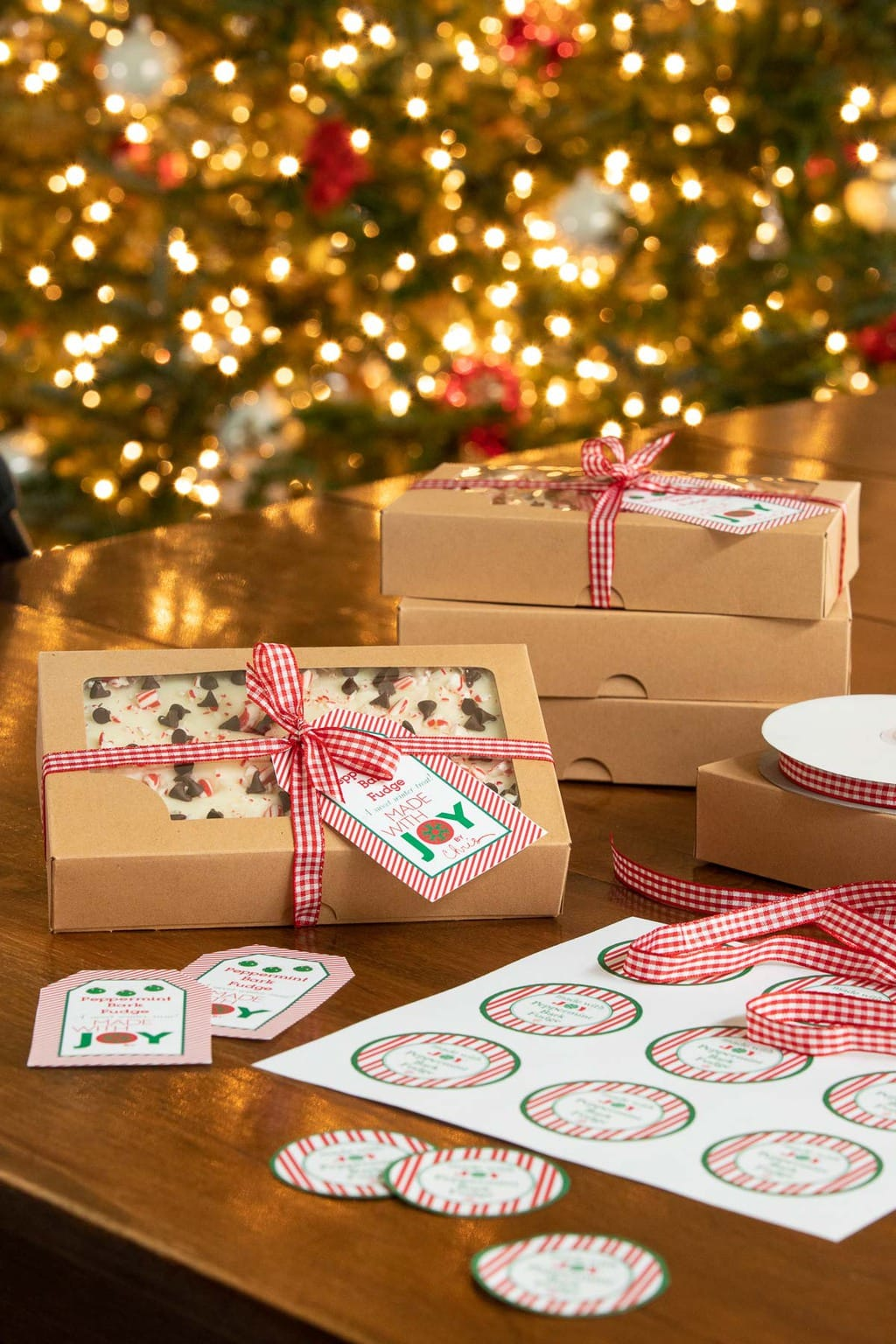 Vertical photo of gift boxes and labels for our Peppermint Bark Fudge with Christmas tree lights in the background.
