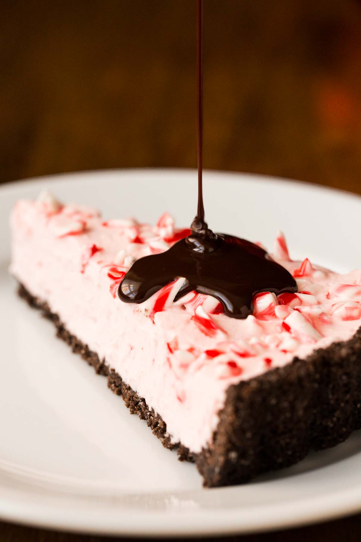 Photo of a slice of Peppermint Candy Cane Tart with chocolate topping being poured over it.