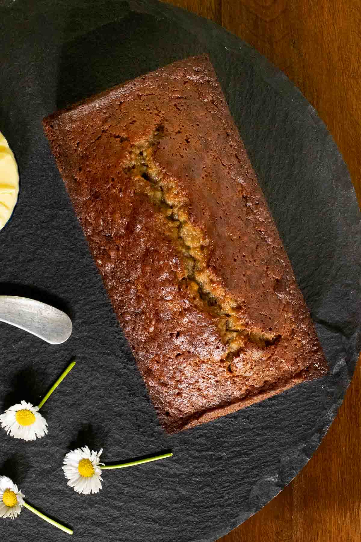 Overhead vertical photo of a loaf of Perfect Banana Bread on a round slate platter.