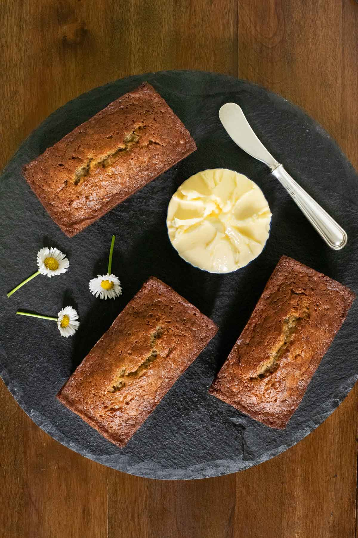 Overhead vertical photo of mini loaves of Perfect Banana Bread on a round dark slate surface.