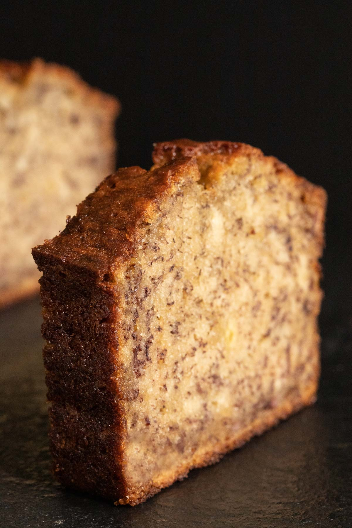 Ultra closeup vertical photo of a slice of Perfect Banana Bread standing up by itself on a dark slate surface.