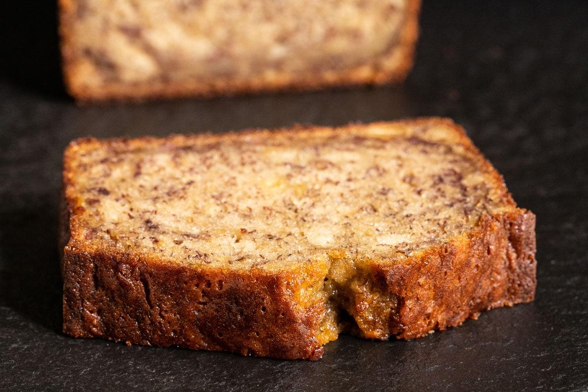 Horizontal closeup photo of a slice of Perfect Banana Bread on a dark gray slate platter.
