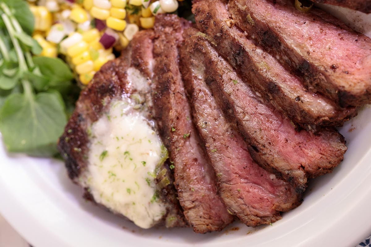 Extreme closeup photo of a Perfectly Grilled Steak with Garlic Lime Butter with fresh corn salad in the background.