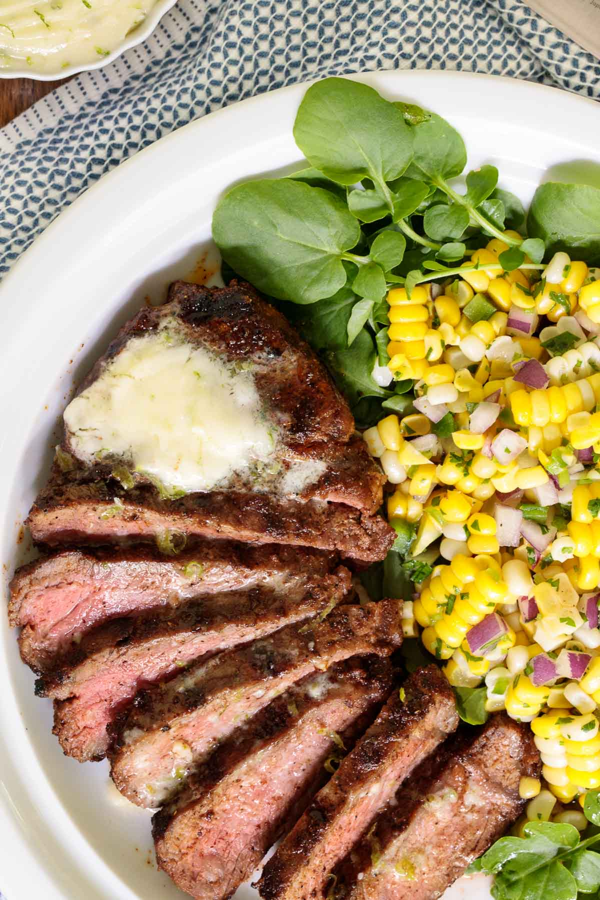 Overhead closeup of a Perfectly Grilled Steak with Garlic Lime Butter with a side of Fresh Corn Salad.