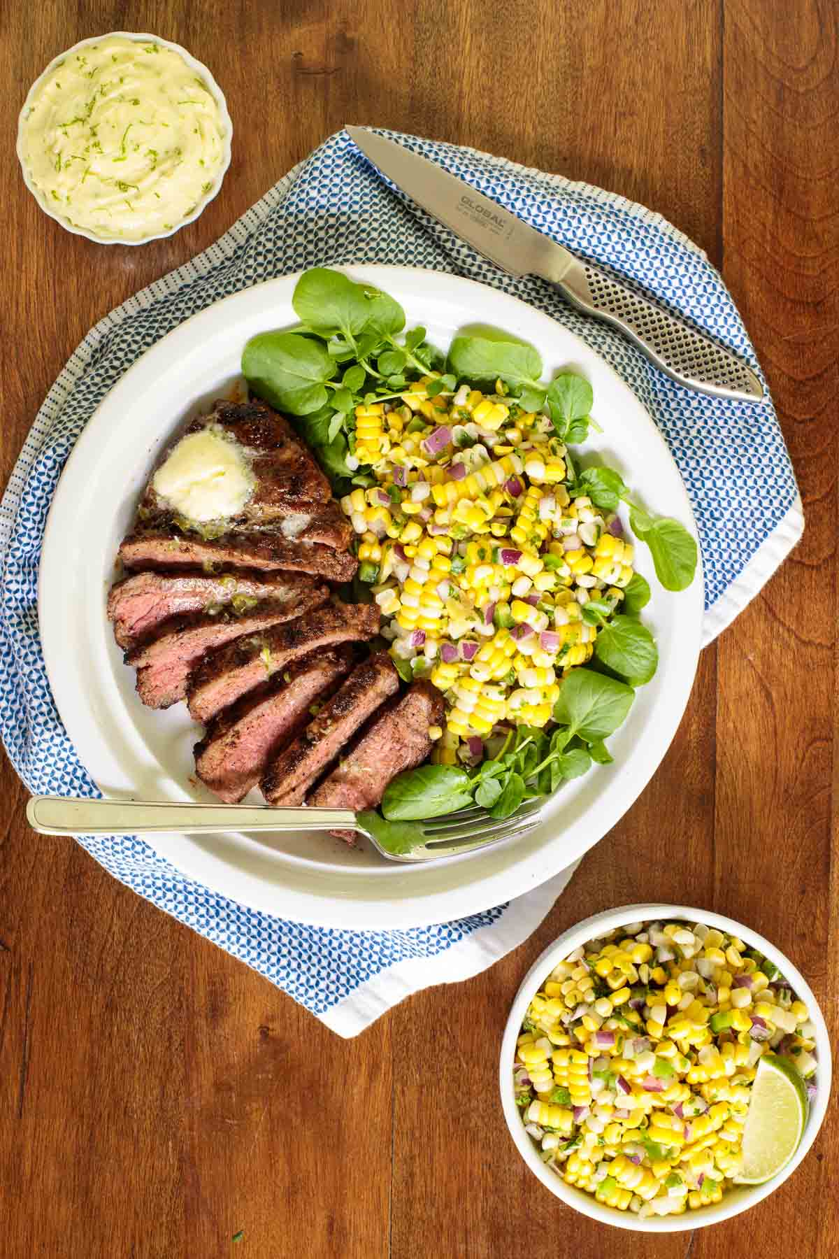 Overhead picture of perfectly grilled steak with corn salad on a wooden table