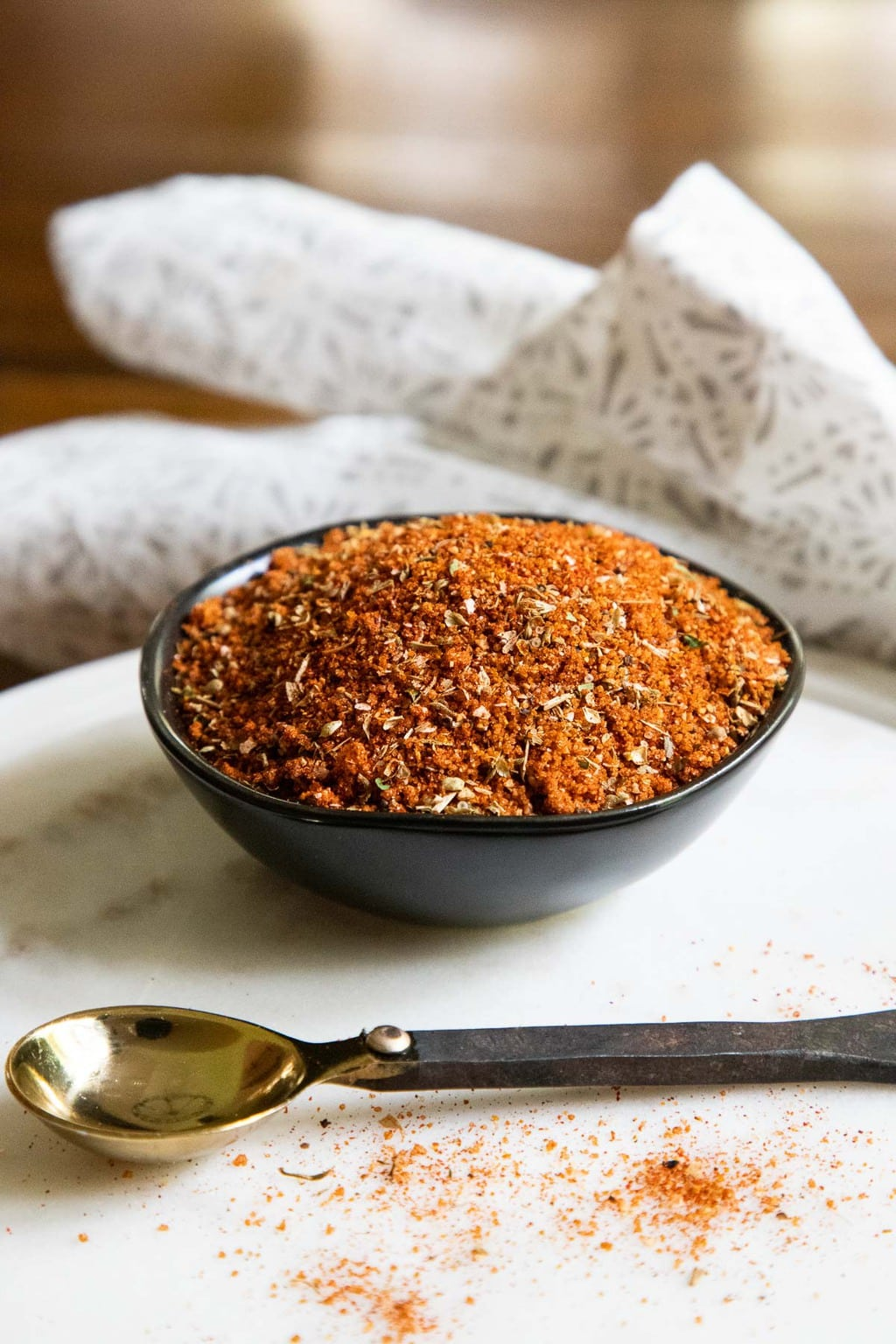 Vertical photo of a small black bowl filled with Peruvian Spice Rub for making Peruvian Chicken.