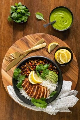 Overhead vertical photo of Peruvian Chicken and Rice Bowls on a round wooden platter.