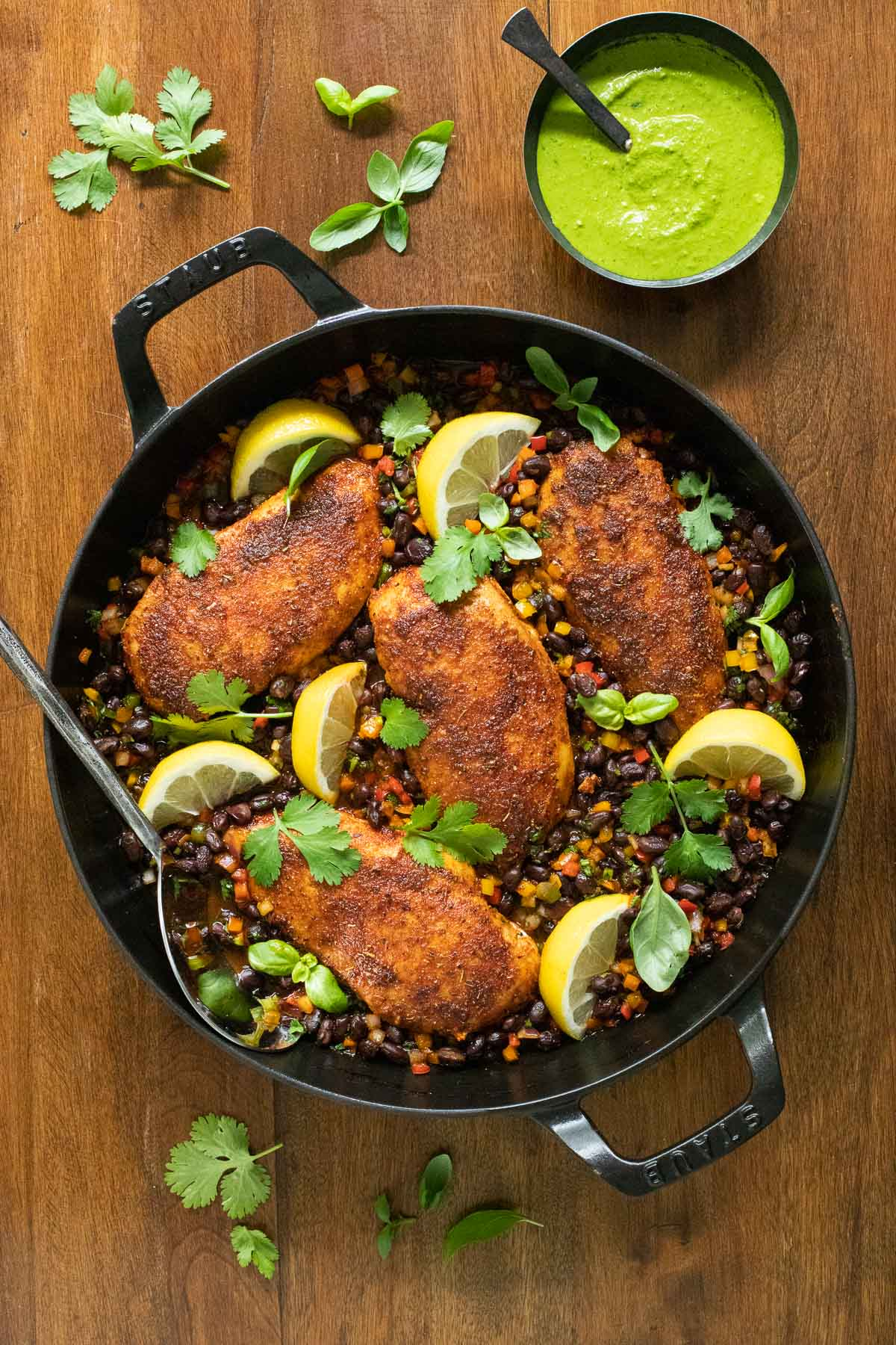 Vertical overhead photo of a Staub frying pan filled with Peruvian Chicken and sauce on a wood table.