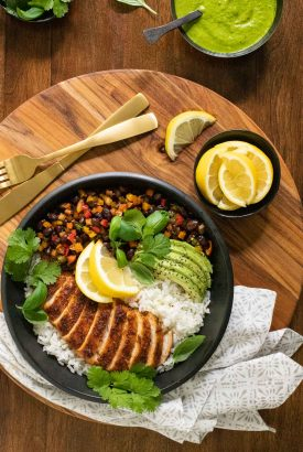 Overhead vertical photo of a Peruvian Chicken Rice Bowl garnished with lemon and avocado wedges and sprigs of fresh cilantro.