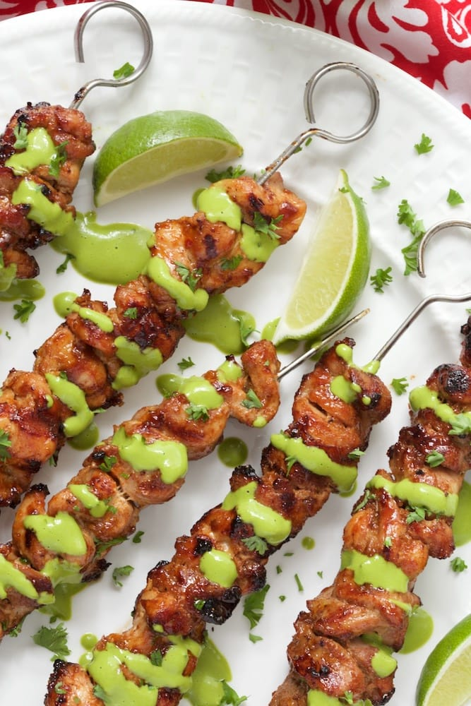 Closeup of Peruvian Grilled Chicken Skewers drizzled with Peruvian Green Sauce drizzled on top and garnished with lime wedges.