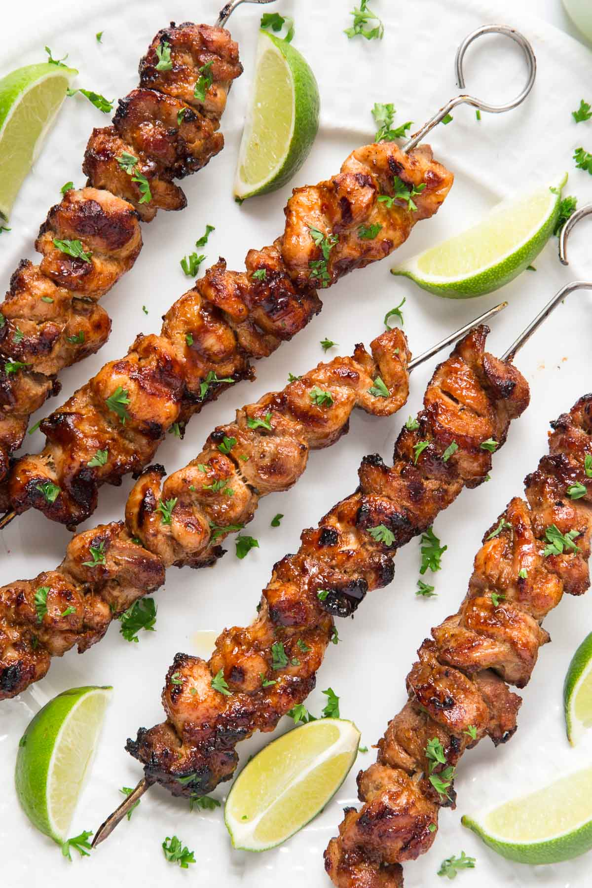 Overhead photo of Peruvian Grilled Chicken Skewers on a white serving platter garnished with cilantro and lime wedges.
