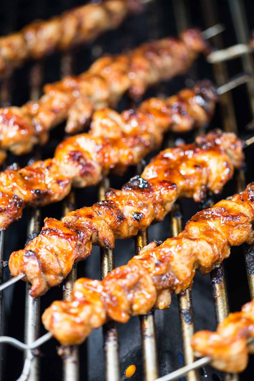 Closeup photo of Peruvian Grilled Chicken Skewers cooking on an outdoor grille.