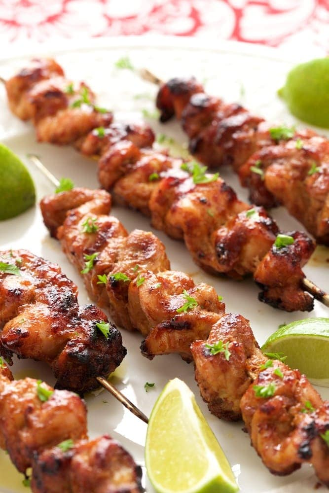 Vertical photo of Peruvian Grilled Chicken Skewers on a white platter garnished with lemon wedges.