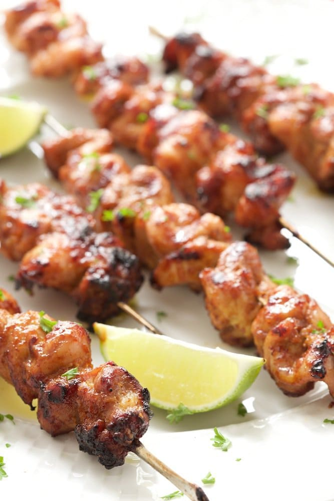 Closeup vertical photo of Peruvian Grilled Chicken Skewers on a white presentation plate garnished with lime wedges and chopped cilantro.