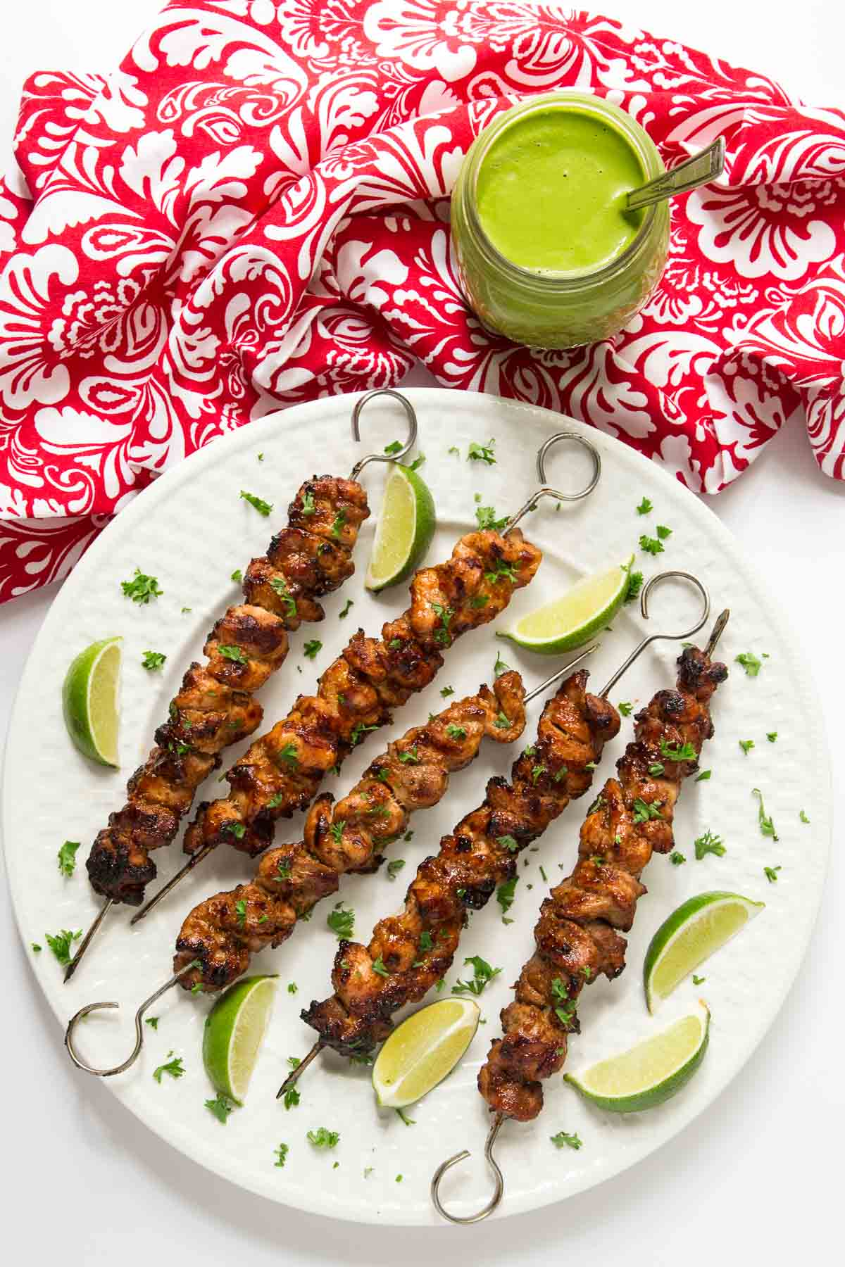 Overhead photo of a serving plate filled with Peruvian Grilled Chicken Skewers.