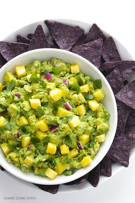 Overhead picture of Pineapple Guacamole with blue corn chips on a white background