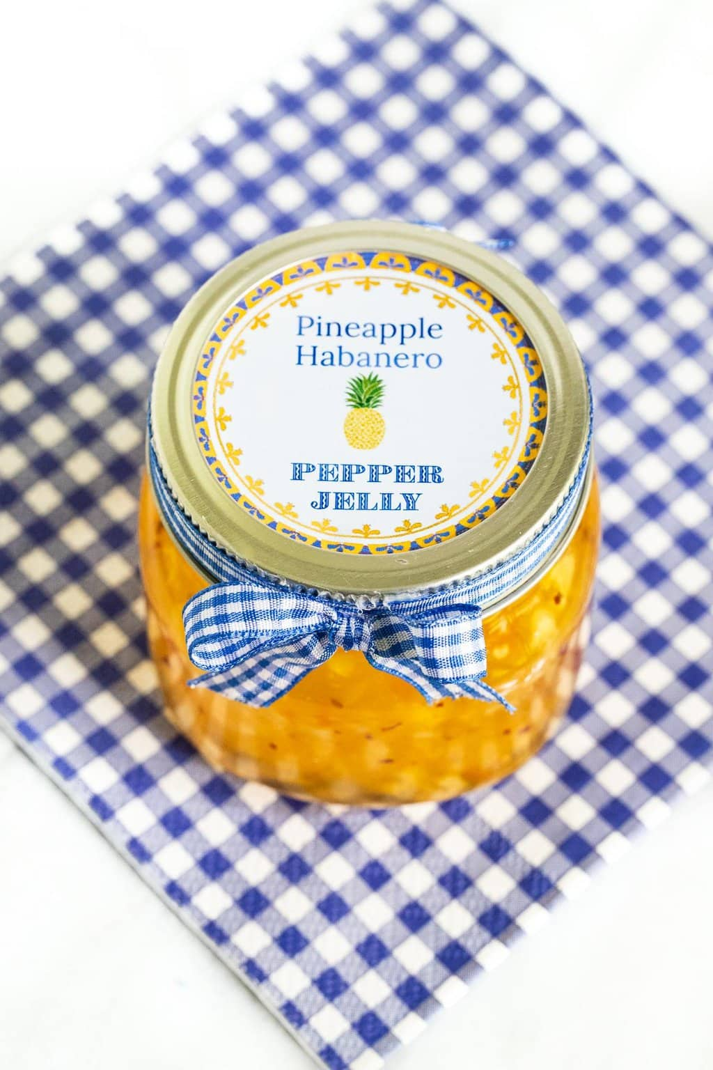 Vertical closeup photo of a jar of Pineapple Habanero Pepper Jelly decorated with a custom label on the lid and a blue and white checkered ribbon bow.