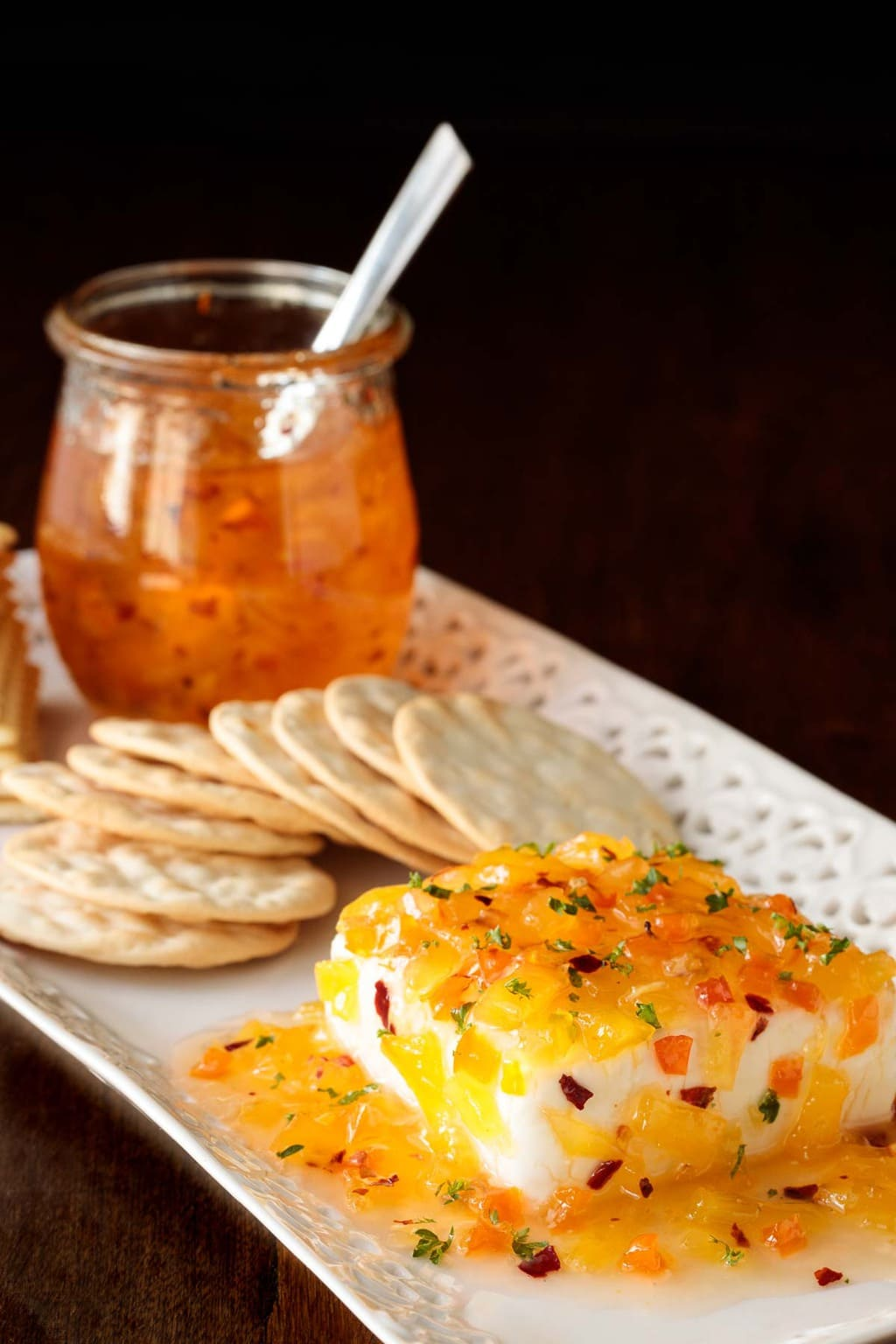 Photo of a white tray filled with crackers, a square of cream cheese and a jar of Pineapple Habanero Pepper Jelly.