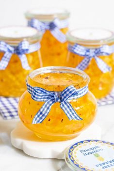 Vertical picture of Pineapple Habanero Pepper Jelly in small glass jars with blue and white ribbon
