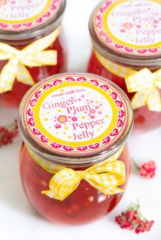 Vertical picture of plum ginger pepper jelly in glass jars with printed labels and yellow ribbons