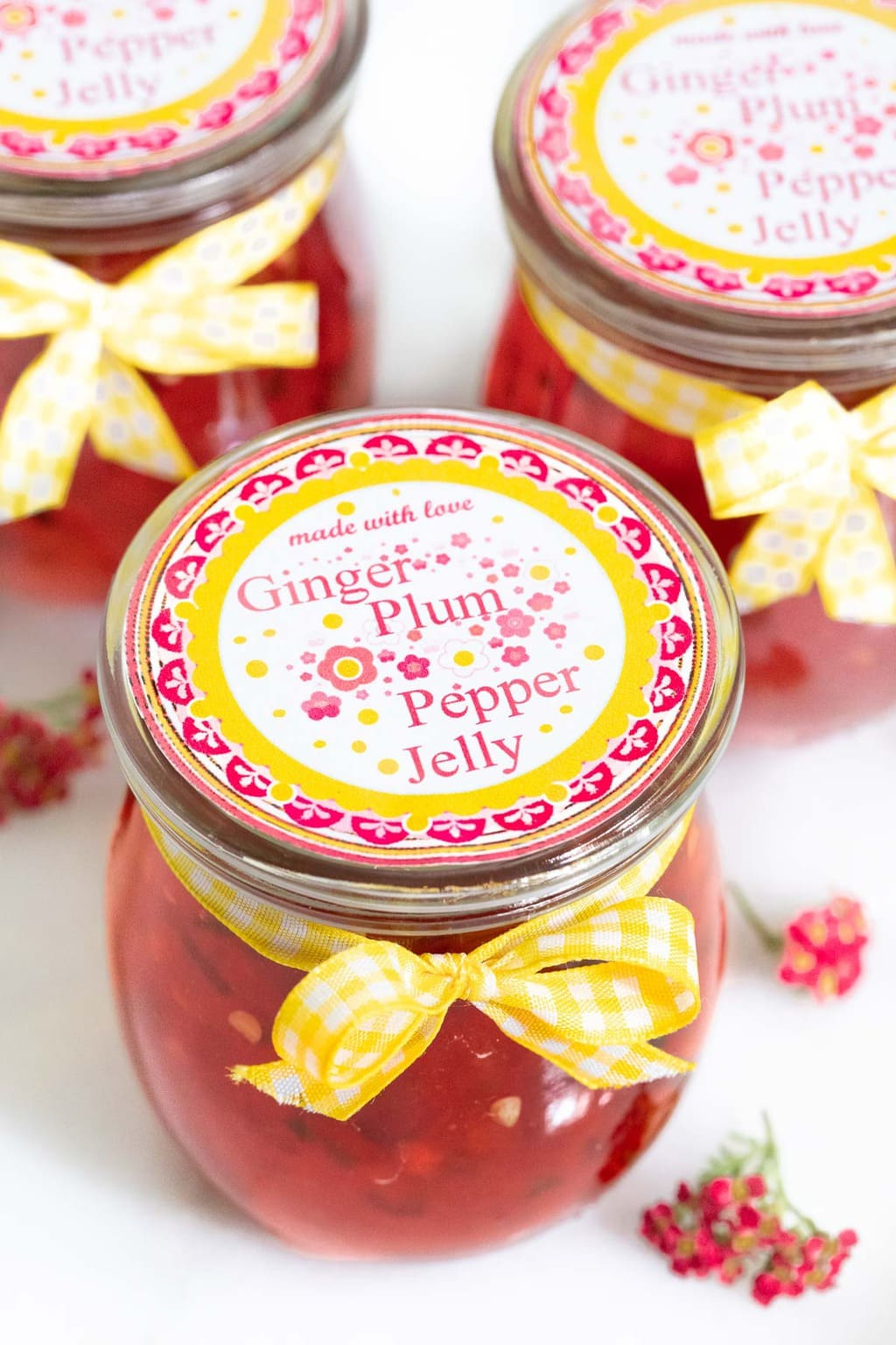 Vertical closeup photo of Plum Ginger Pepper Jelly in glass Weck jars with printed labels and yellow ribbons.