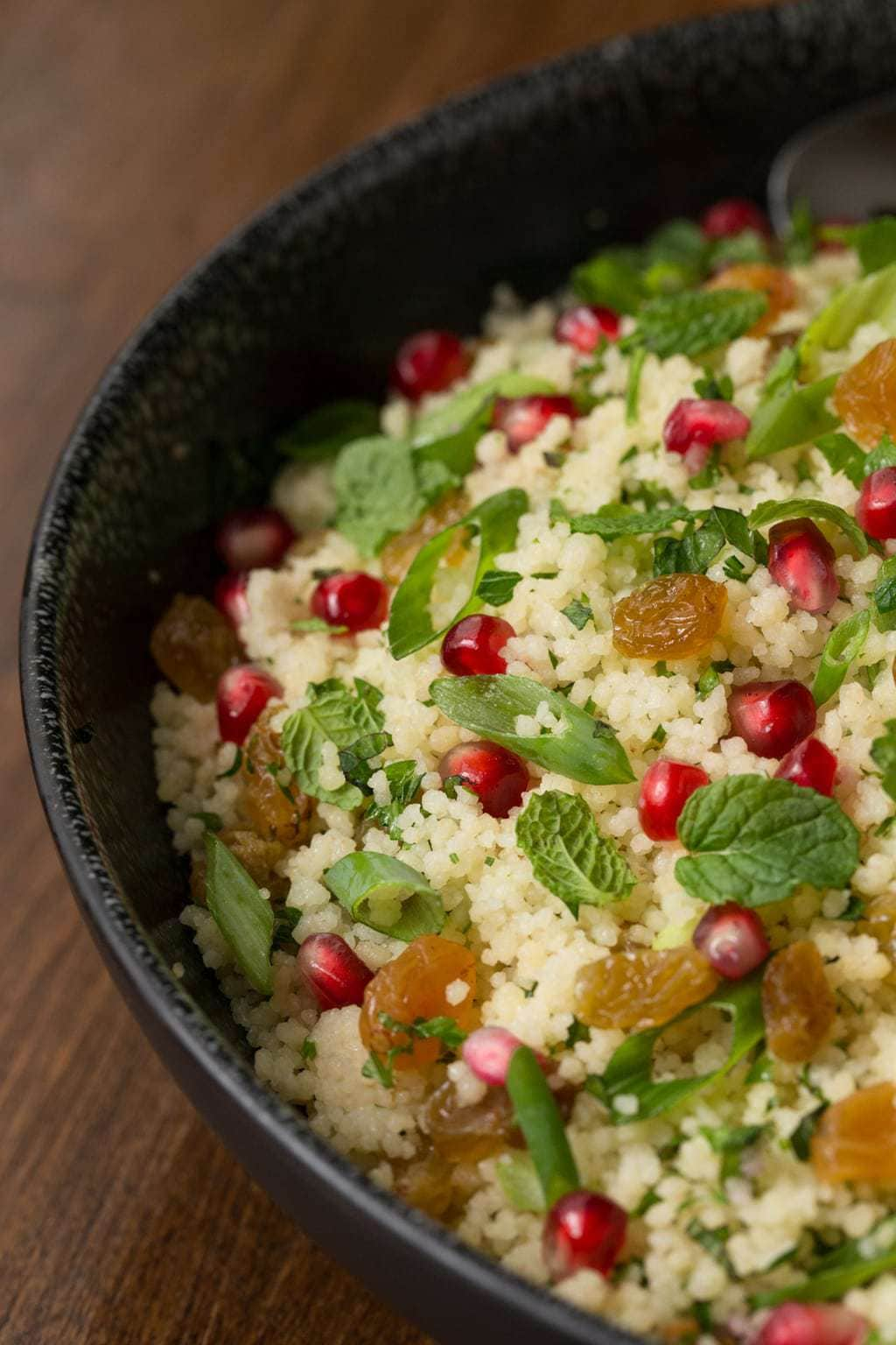 Close up vertical photo of a Pomegranate Parsley Couscous Salad presented in a black bowl.