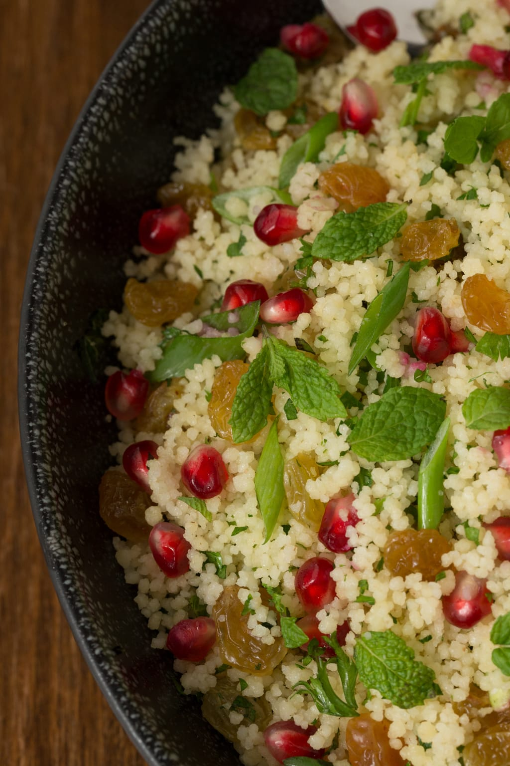 Closeup overhead photo of a bowl Pomegranate Parsley Couscous Salad.