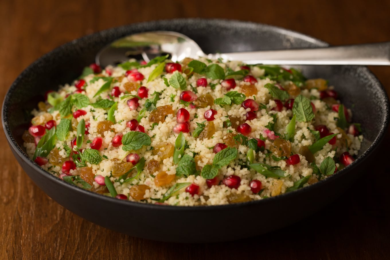 Photo of a black bowl of Pomegranate Parsley Couscous Salad on a wood table.