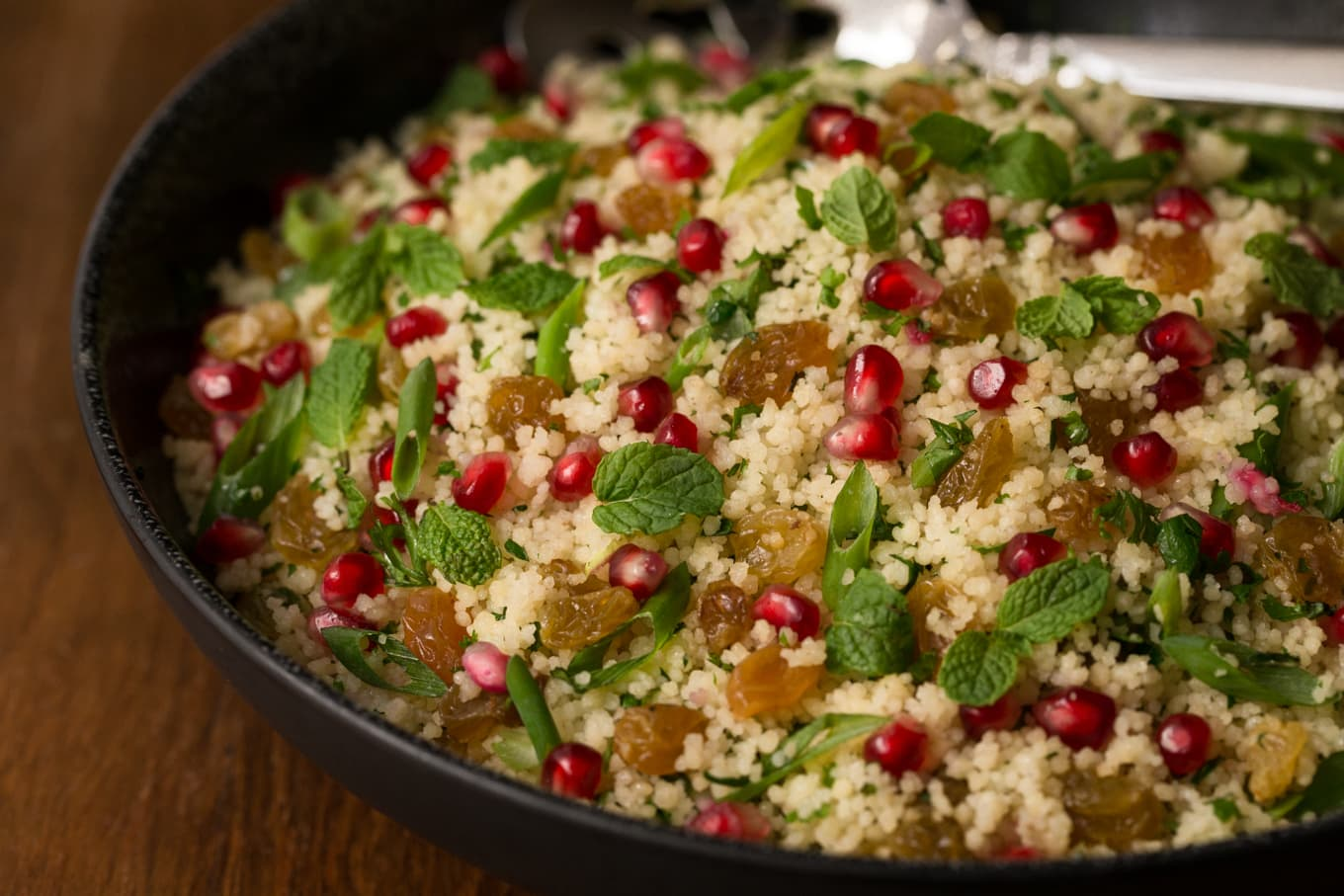 Photo of a bowl of Pomegranate Parsley Couscous Salad on a wood table.