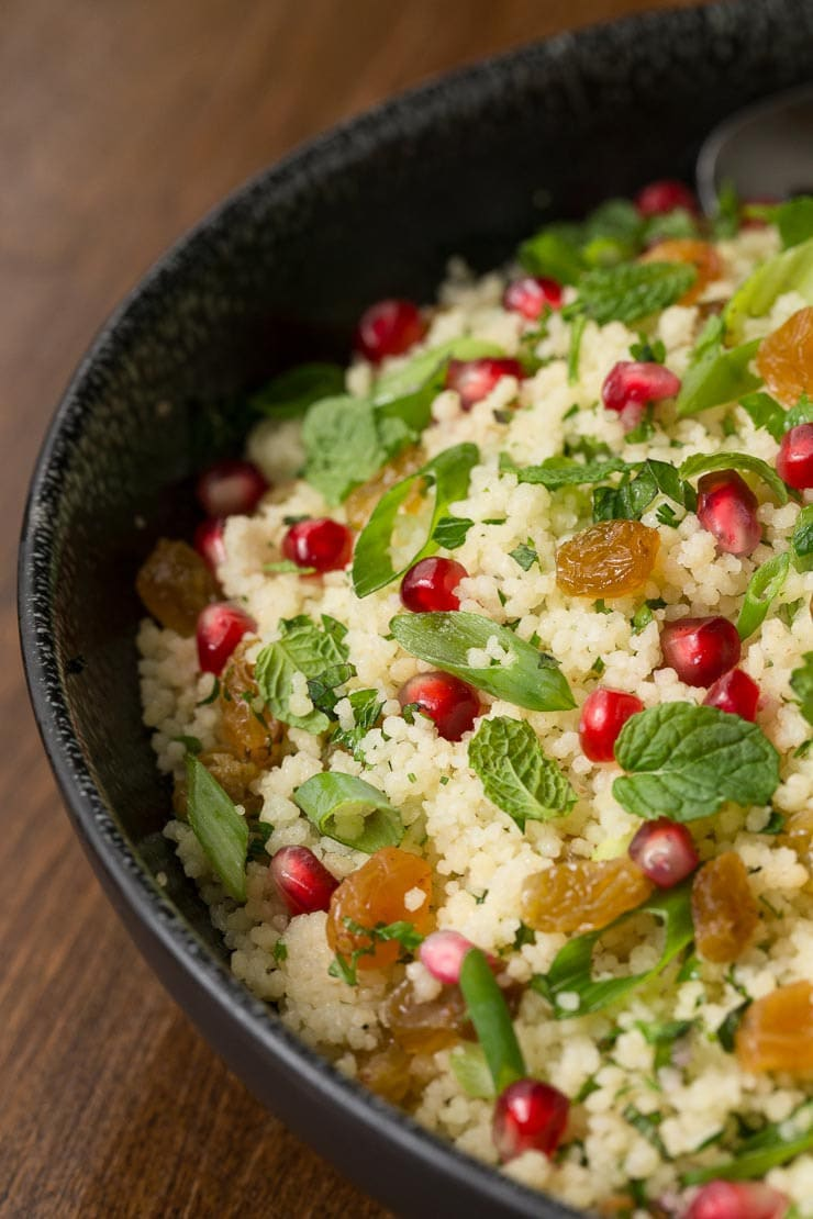 Photo of a black serving bowl filled with Pomegranate Parsley Couscous Salad on a wood table.