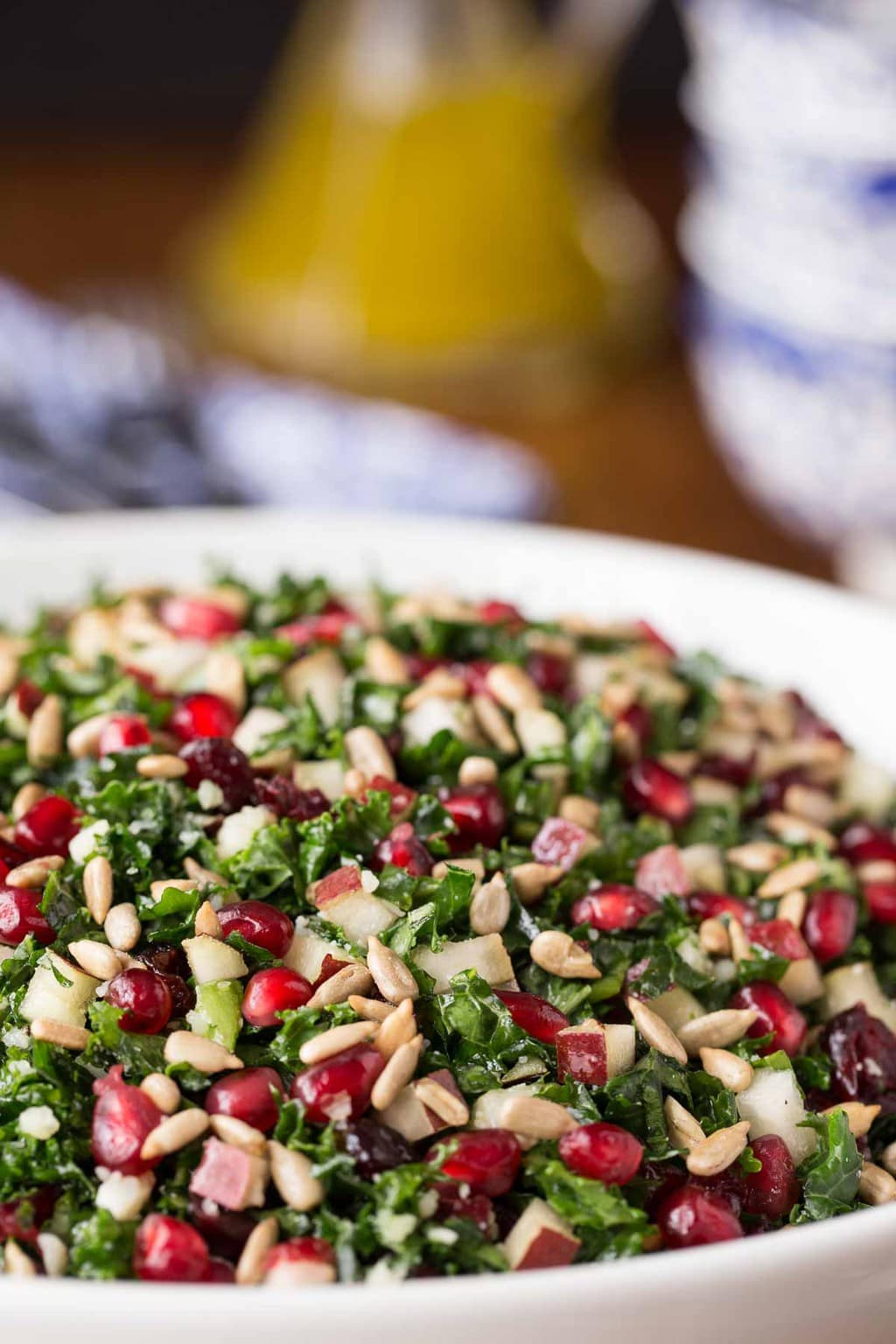 Photo of a white serving bowl filled with Pomegranate Pear Kale Salad.