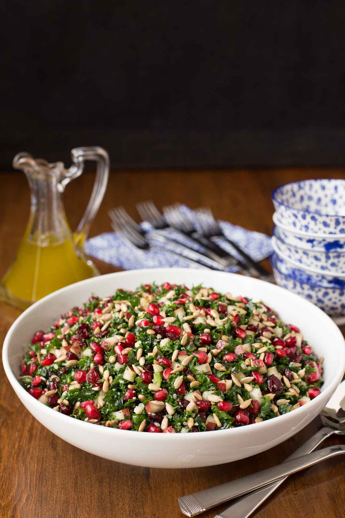 Vertical picture of Pomegranate Pear Salad in a white bowl with blue and white dishes stacked and dressing in a glass cruet in the background