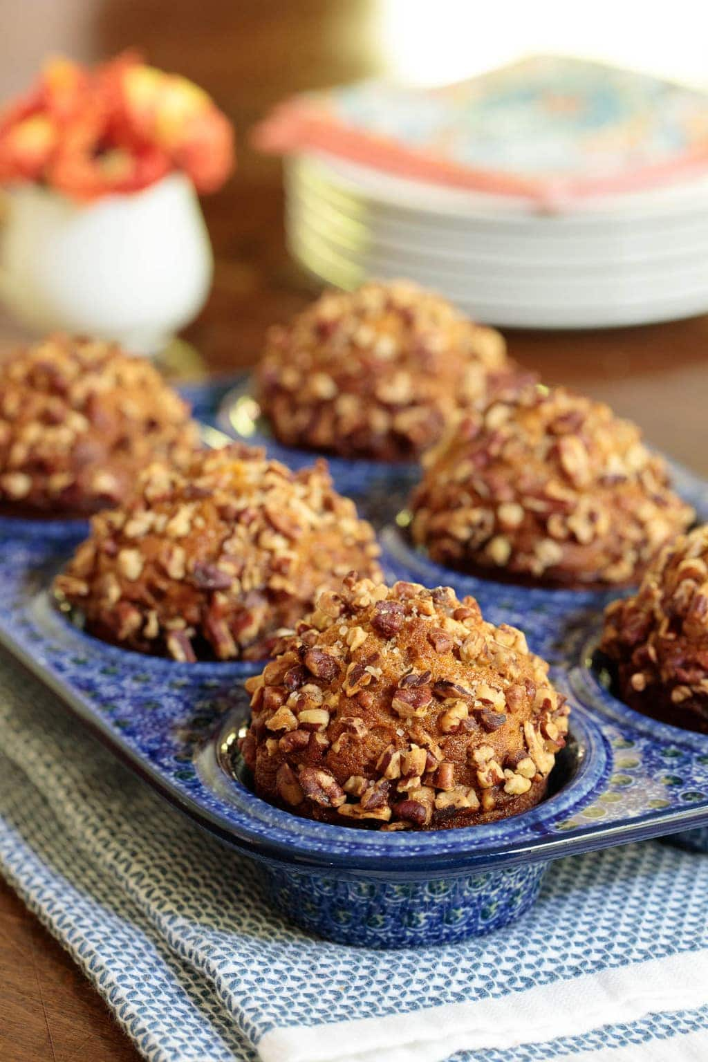 Photo of a decorative pottery muffin pan filled with Easy Praline Pumpkin Muffins.
