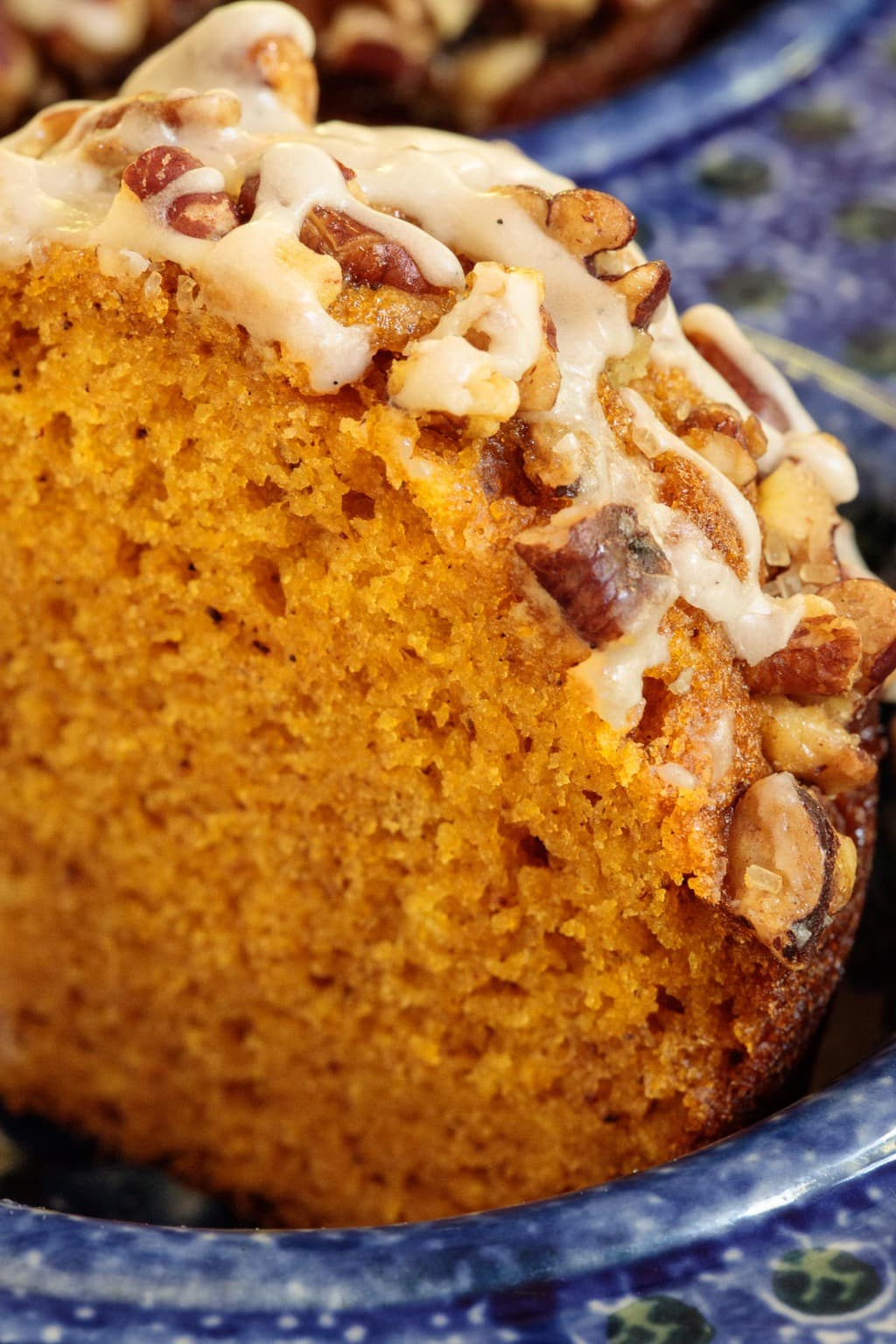 Vertical extreme closeup photo of the inside of an Easy Praline Pumpkin Muffin on a blue porcelain muffin baking tray.