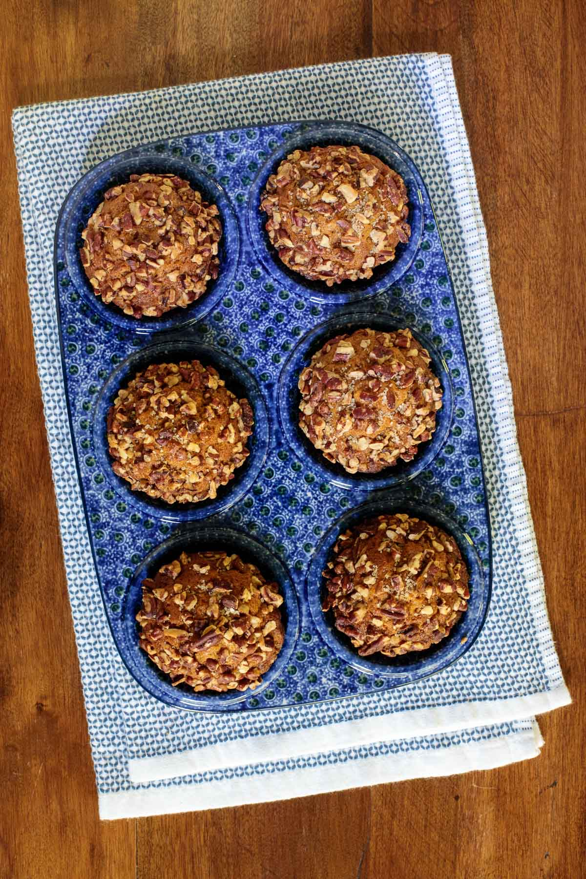 Overhead vertical photo of a blue and white decorative muffin pan filled with Easy Praline Pumpkin Muffins on a wood table.