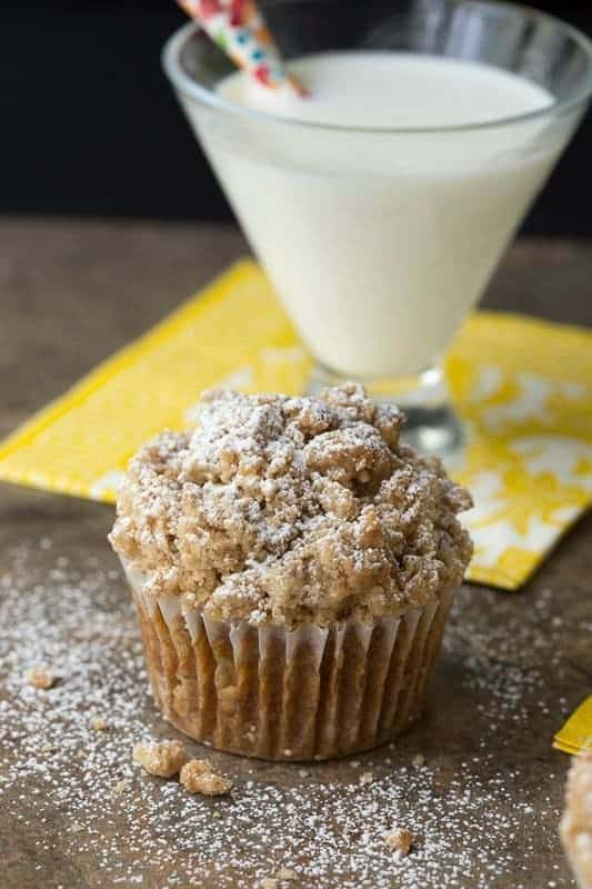 Closeup of a Pumpkin Crumb Muffin with a glass of milk with a straw on a yellow napkin in the background.