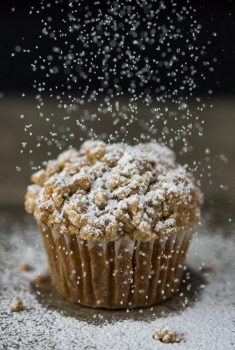 Vertical picture of Pumpkin Crumb Muffin on a black background with powdered sugar on top